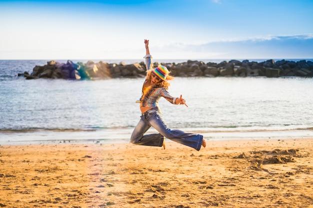 Heureuse liberté folle femme d'âge moyen sauter sur la plage pour le bonheur et la joie de vivre vacances en plein air concept océan et plage d'été