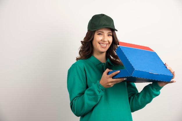 Heureuse livreuse ouvrant la boîte à pizza sur blanc.