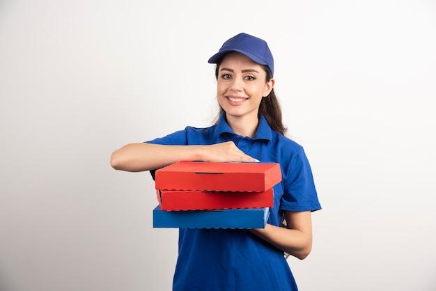 Heureuse Livreuse Souriante En Uniforme Bleu Avec Des Boîtes De Pizza à Emporter Sur Fond Blanc. Photo De Haute Qualité Photo gratuit