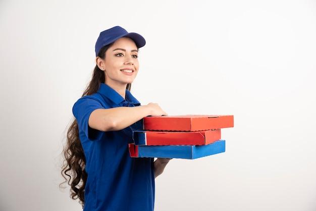 Heureuse livreuse souriante en uniforme bleu avec des boîtes de pizza à emporter sur fond blanc. photo de haute qualité