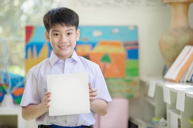 Heureuse main de garçon asiatique tenant un carton blanc et en regardant la caméra
