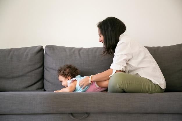 Heureuse maman aux cheveux noirs câlins jolie petite fille sur un canapé gris. vue de côté. concept de parentalité et d'enfance