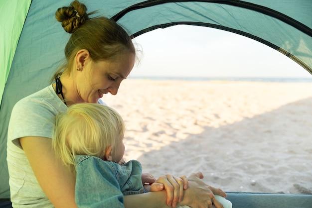 Heureuse maman avec enfant reste dans la tente touristique. vue mer et plage.
