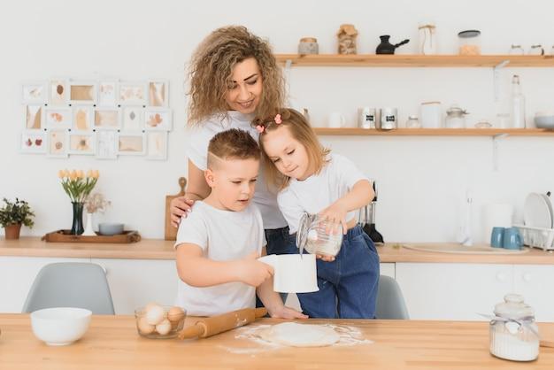 Heureuse maman et enfants mélangeant les ingrédients pour la pâte à gâteau, à tarte ou à biscuits maison dans la cuisine.