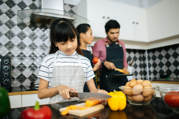 Heureuse maman enseigne à sa fille hacher des légumes préparant des ingrédients