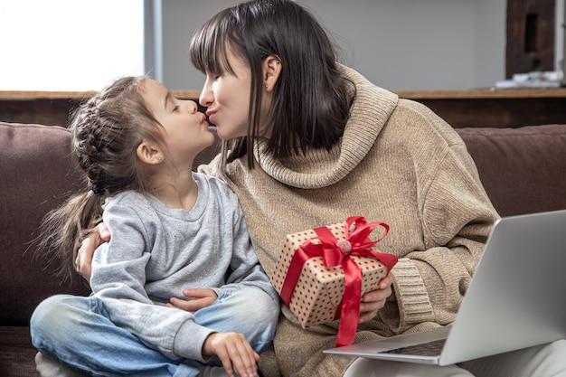 Heureuse maman et fille s'embrassent. le concept de félicitations pour les vacances, les relations familiales et le temps de qualité ensemble.