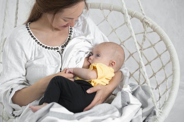 Heureuse maman nourrit le bébé dans un hamac blanc. concept de maternité heureuse.