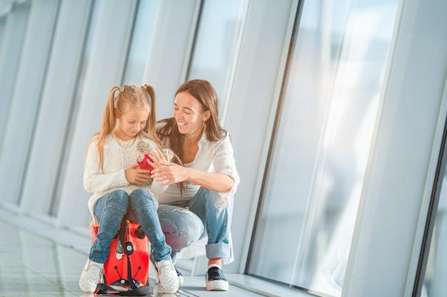 Heureuse maman et petite fille avec carte d'embarquement à l'aéroport