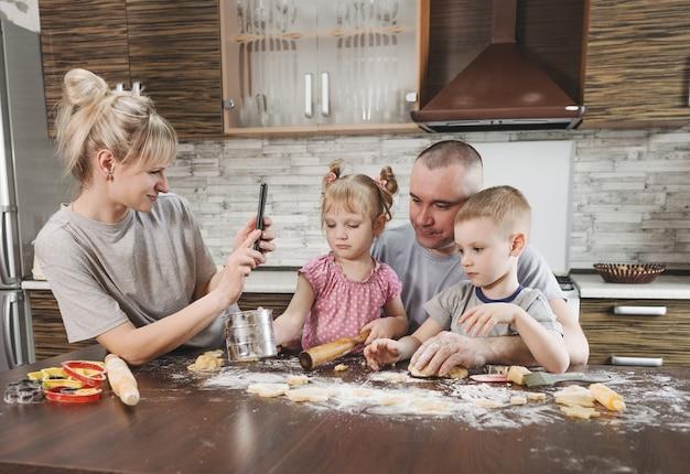 Heureuse maman prend des photos de papa avec deux jeunes enfants dans la cuisine tout en faisant des biscuits à la farine. famille heureuse, cuisiner ensemble