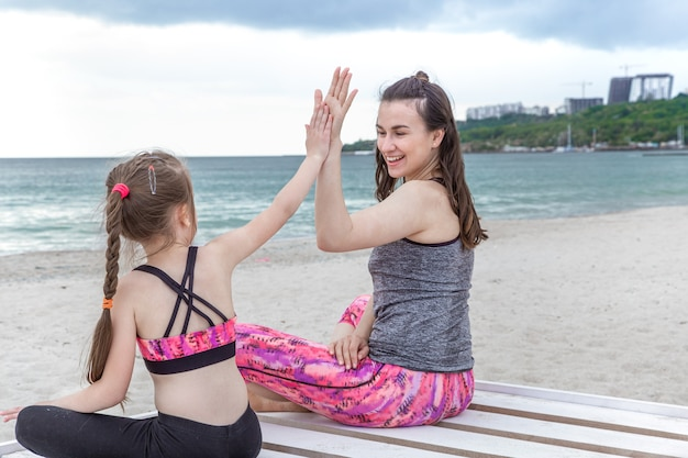 Heureuse maman et sa fille en vêtements de sport pratiquent le yoga au bord de la mer. des valeurs familiales et un mode de vie sain.
