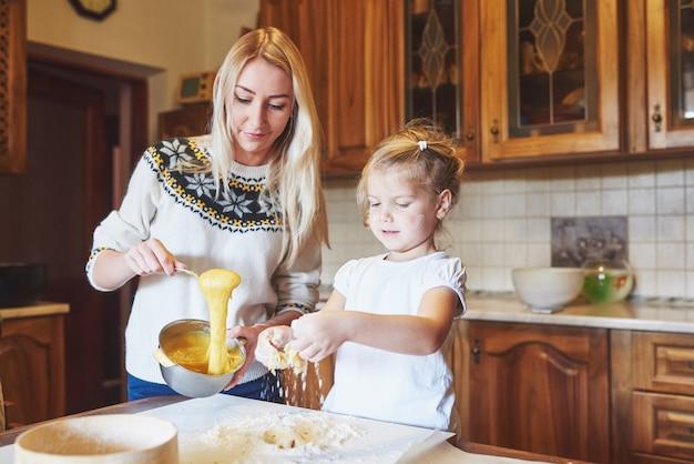 Heureuse maman souriante dans la cuisine prépare des cookies avec sa fille.