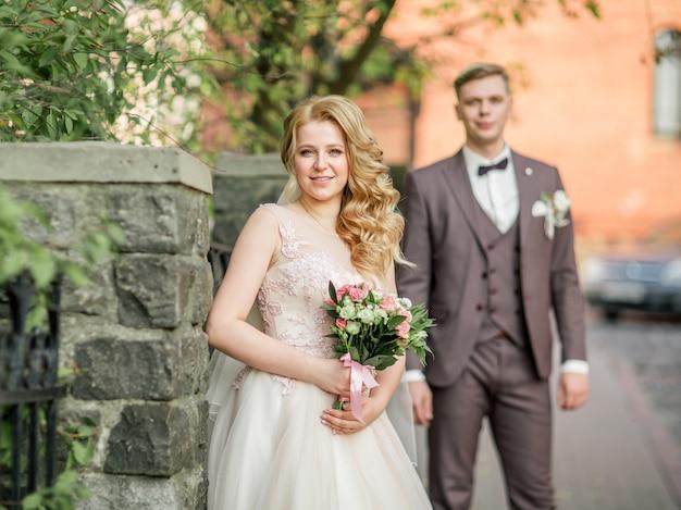 Heureuse mariée avec bouquet de mariage debout sur la rue de la ville. vacances et événements