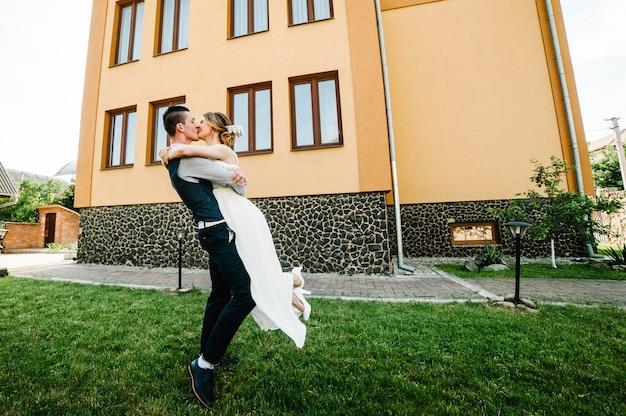 Heureuse mariée élégante, tenue de marié ramassée dans les mains et dansant. mariage première danse