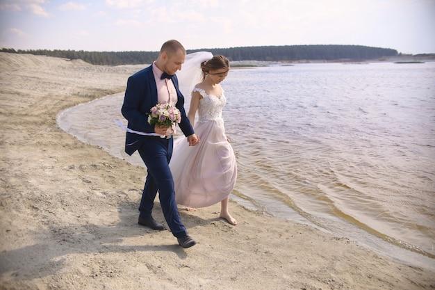 Heureuse mariée et le marié courent le long du lac