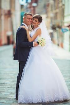 Heureuse mariée et le marié dansant dans une rue