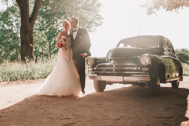 Heureuse mariée et le marié debout sur le bord de la route. vacances et événements