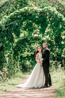 Heureuse mariée et le marié debout sous l'arche de mariage