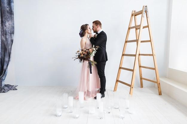 Heureuse mariée et le marié sur l'échelle au studio. fond de mur blanc isolé