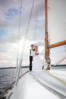 Heureuse mariée et le marié étreignant sur un yacht