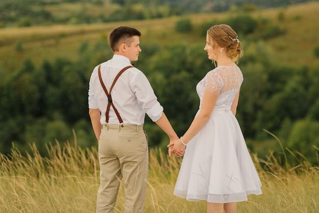 Heureuse mariée et le marié, main dans la main et debout devant une belle vue sur la nature. jour de mariage.