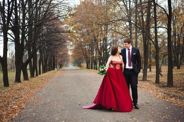 Heureuse mariée et le marié marchant dans la forêt d'automne