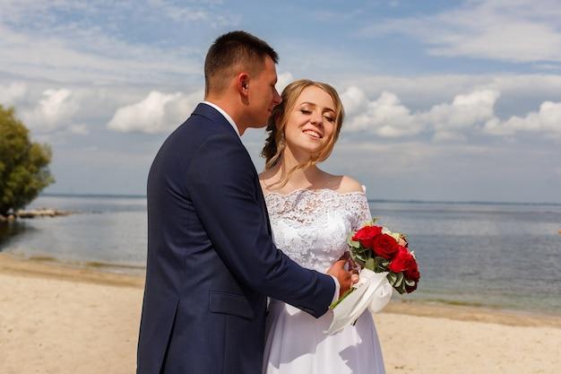 Heureuse mariée et le marié marchant le long de la rivière. promenade romantique des jeunes mariés sur la plage de sable en journée ensoleillée. couple de mariage sur la côte de la mer. jour du mariage à l'extérieur. mariée et groon souriant étreindre et s'embrasser