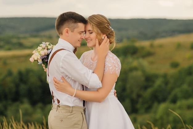 Heureuse mariée et le marié s'amusent contre de beaux paysages de la nature. jour de mariage.