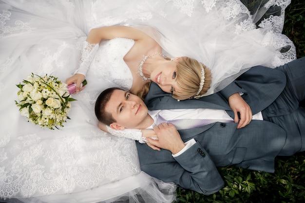 Heureuse mariée et le marié sont couchés sur l'herbe verte