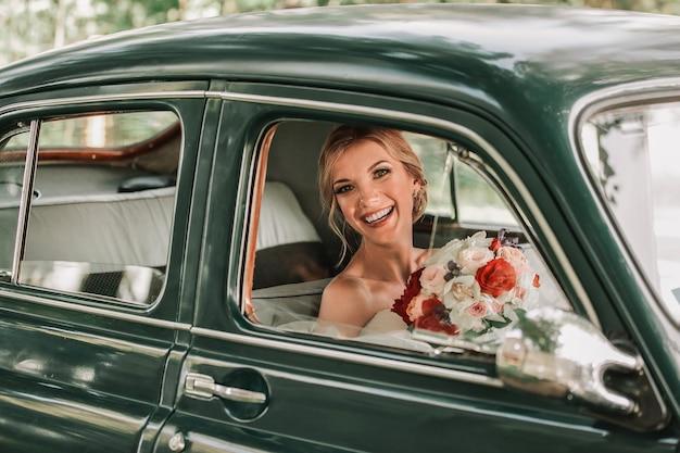 Heureuse mariée regardant par la fenêtre de la voiture. vacances et événements