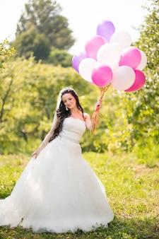 Heureuse mariée en robe avec des ballons colorés dans le parc verdoyant