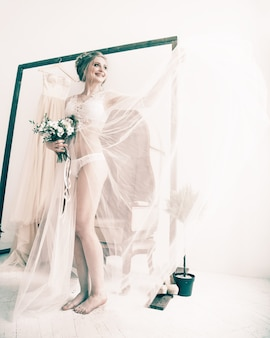Heureuse mariée en robe boudoir debout dans une chambre d'hôtel spacieuse. matin de la mariée.