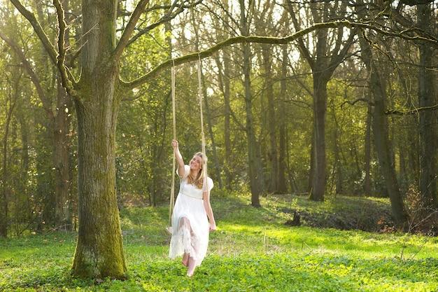 Heureuse mariée en robe de mariée blanche assis sur un swin dans les bois