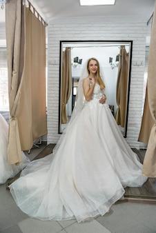Heureuse mariée en robe de mariée debout dans le salon