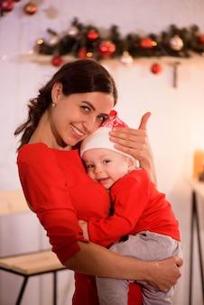 Heureuse mère et adorable bébé en bonnet de noel célèbrent noël