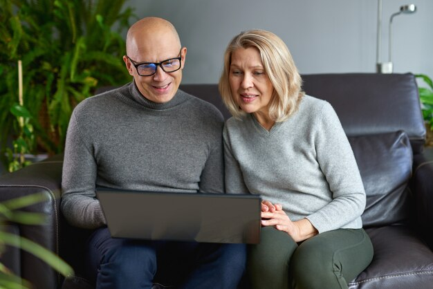 Heureuse mère âgée s'asseoir reste sur le canapé avec son fils adulte regarder une vidéo drôle sur un ordinateur portable moderne