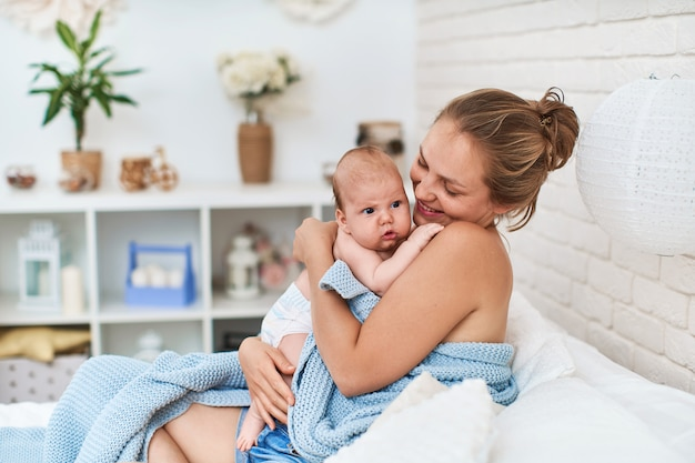 Heureuse mère aimante est assise sur le lit avec un petit bébé, après l'allaitement.