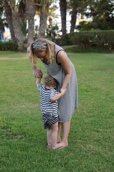 Heureuse mère aimante et son fils jouant et s'embrassant. promenade en famille près des palmiers. hôtel de plage en turquie. l'heure d'été ensemble, la lumière du soleil. bonne fête des mères.