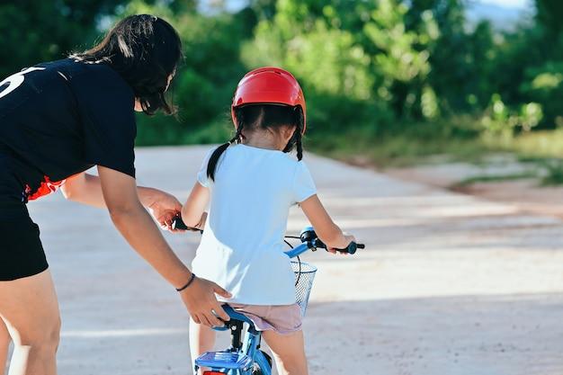Heureuse mère apprenant à sa petite fille à faire du vélo.