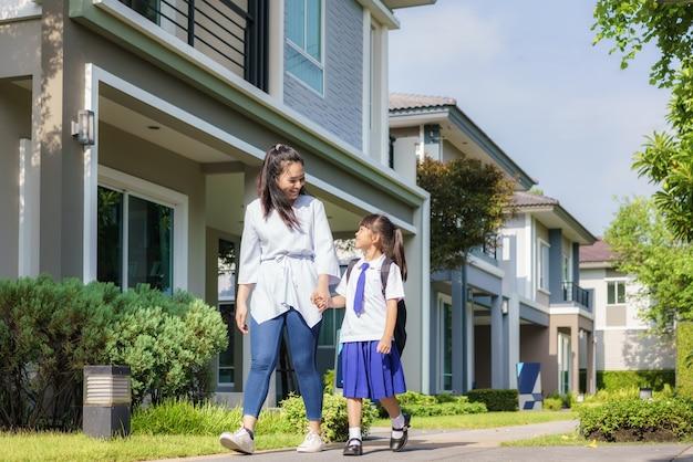 Heureuse mère asiatique et élève de l'école primaire fille marchant à l'école dans la routine scolaire du matin pour la journée dans la vie se préparant pour l'école.