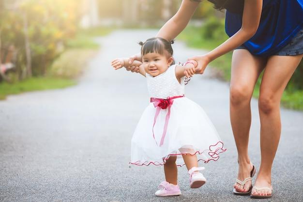 Heureuse mère asiatique et mignonne petite fille marchant avec plaisir et amour