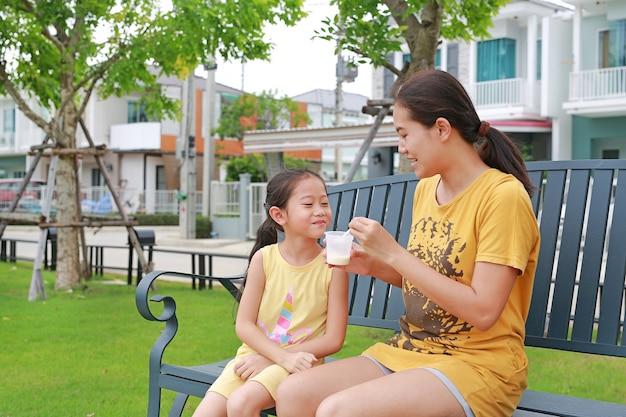Heureuse mère asiatique nourrir sa fille et se détendre assis sur un banc dans le jardin en plein air