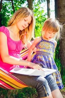 Heureuse mère avec un bébé dans un hamac lisant un livre sur la nature de la bible dans le parc