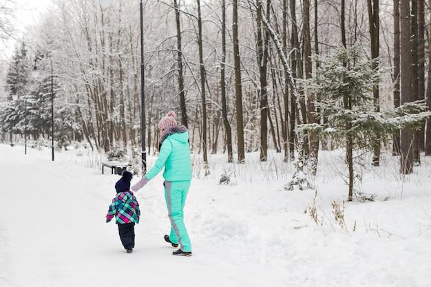 Heureuse mère et bébé dans le parc d'hiver. famille à l'extérieur. maman joyeuse avec son enfant.