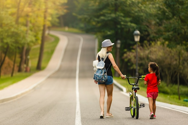 Heureuse mère et bébé fille s'amuser dans le parc à vélo