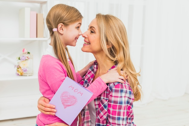 Heureuse mère avec carte de voeux touchant les nez avec sa fille