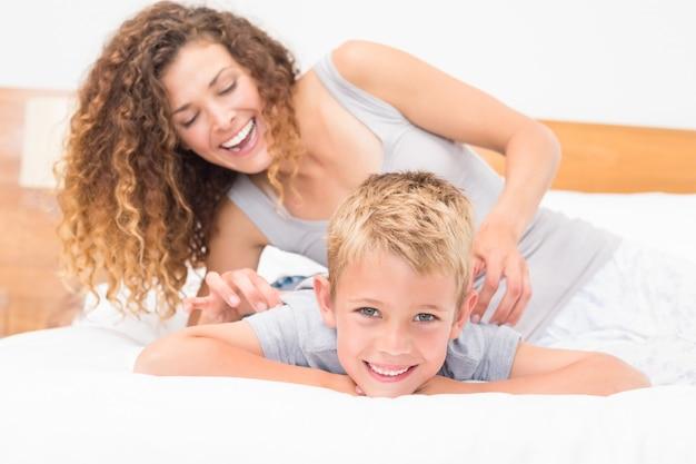 Heureuse mère chatouillant son fils mignon sur le lit