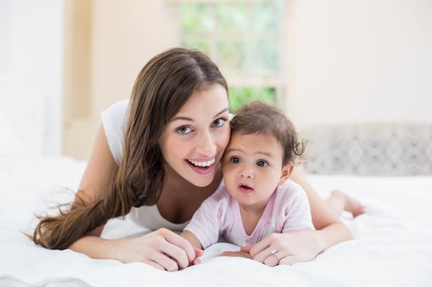 Heureuse mère couchée avec bébé à la maison