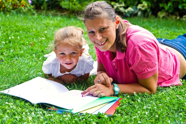 Heureuse mère dessiner un livre avec une petite fille dans le jardin