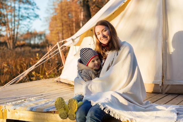 Heureuse mère embrasse son enfant avec une couverture tout en étant assis près d'une tente de camping