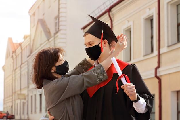 Heureuse mère embrasse son fils étudiant en robe de graduation et une casquette carrée après la cérémonie de remise des diplômes ils portent des masques de protection sur le territoire de l'établissement d'enseignement